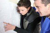 Electrician and apprentice checking diagram — Stock Photo