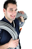 Electrician stood with corrugated cabling — Stock Photo