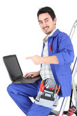 Man sitting on ladder with laptop and plumbing tools — Stock Photo