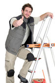 Tiler climbing ladder whilst giving the thumbs-up — Stock Photo