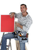 Carpenter posing with red poster — Stock Photo