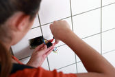Female electrician wiring a wall socket — Stock Photo
