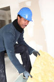 Construction worker insulating wall — Stock Photo