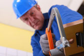 Plumber sawing pipe — Stock Photo