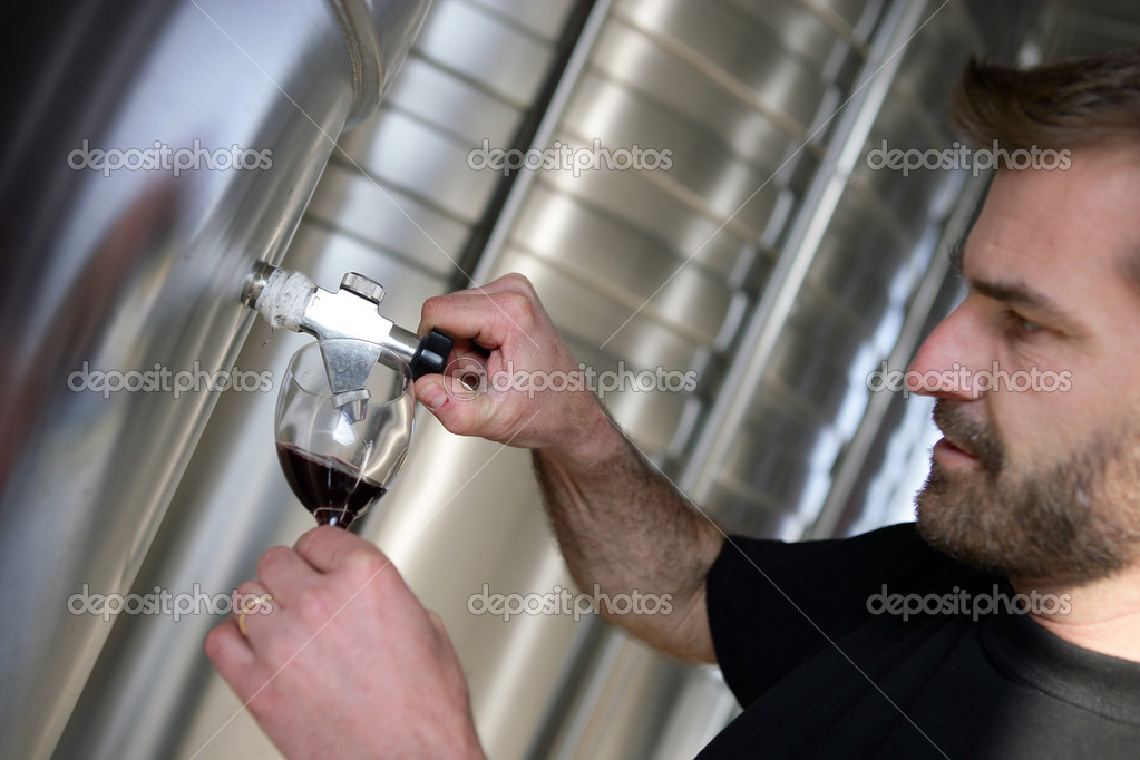 Man sampling red wine from tap — Stock Photo #11798455