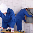 Stock Photo: Two plumbers working in a public bathroom
