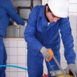 Two plumbers hard at work - Stock Photo