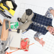 Royalty-Free Stock Photo: Tradesman posing with a metal grid, tools, and building materials