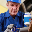 Plumber gluing grey plastic pipe - Stock Photo