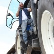 Farmer on a tractor using a mobile phone — Stock Photo