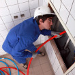 Stock Photo: Electricifeeding cable up behind tiled wall