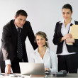 Three office workers around a desk — Stock Photo