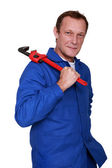 Plumber holding wrench over shoulder — Stock Photo