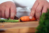 Close-up of chef slicing carrot — Stock Photo