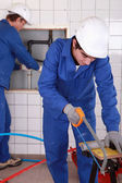 Two plumbers hard at work — Stockfoto