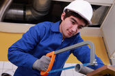Young man sawing tube — Stock Photo