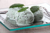 Three scoops of mint choc chip ice cream on a square plate — Stock Photo