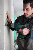 Handyman drilling into panel — Stockfoto