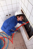 Electrician feeding cable up behind a tiled wall — Stock Photo