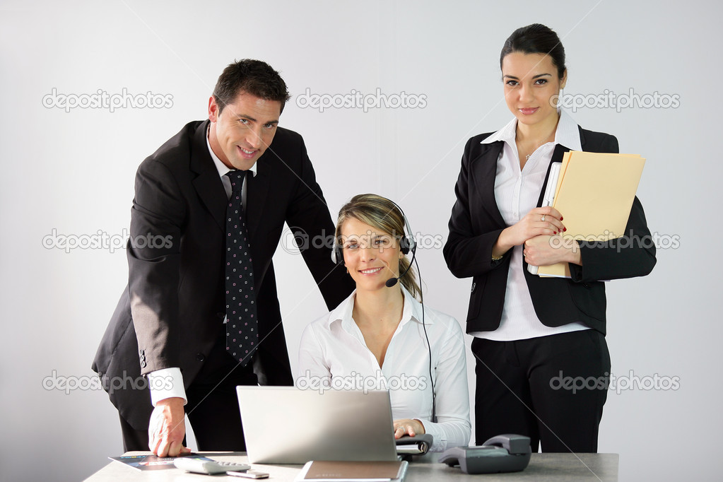 Three office workers around a desk  Stock Photo #11809968