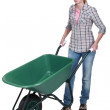 Female construction worker with a wheelbarrow — Stock Photo #11810410