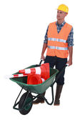 Man with wheelbarrow full of traffic cones — Stock Photo