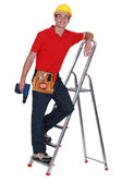 Young tradesman standing on a stepladder and holding a screw gun — Stock Photo