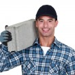 A man carrying a breeze block. - Stockfoto