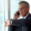 Stock Photo: Businessmchecking time whist on telephone call