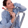 Woman with paintbrush in hand — Stock Photo