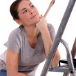 Woman with paint brush leaning on ladder — Stock Photo #11845961