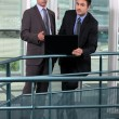 Foto Stock: Businessmen, using laptop on hall