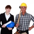 Studio shot of young female architect and mature carpenter — Stock Photo