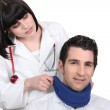 Female doctor applying a neck brace to a male patient — Stock Photo