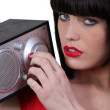 Stock Photo: Brunette tuning radio
