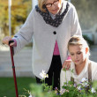 Elderly woman in a garden with a young helper — Stock Photo #11846642
