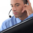 Businessman wearing a headset - Stock Photo