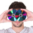 Young man holding compact discs to his face - Stock Photo