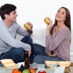Couple eating hamburgers — Stock Photo