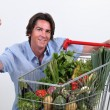 Man kneeling by trolley full of vegetables - Stock Photo