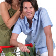Couple with trolley full of vegetables — Stock Photo
