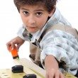 Stock Photo: Little boy pretending to be carpenter