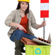 Stock Photo: Female construction worker warning you to recycle old material