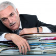 Stock Photo: Businessmlying over pile of documents