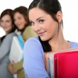 Attractive female students holding folders and books — Stock Photo #11847228
