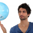 Man spinning a globe - Stockfoto