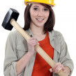 Female labouror holding sledge hammer - Stockfoto