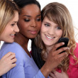 Girlfriends with a mobile phone — Stock Photo