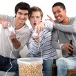 Three male teenagers playing video games. - Stock Photo