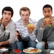 Male friends eating burgers and watching sport on TV — Stock Photo